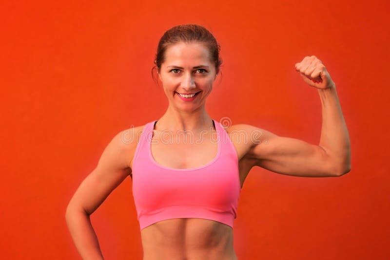 Mulher atlética nova que levanta na frente da parede vermelha, mostrando um de foto de stock