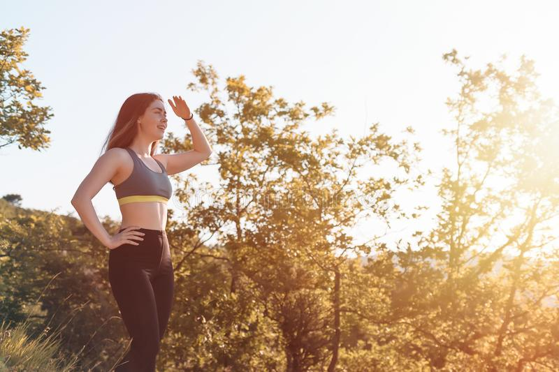 Mulher atlética nova que olha na distância Floresta no fundo Conceito de seguimento dos esportes, da aptidão e do estilo de vida  foto de stock