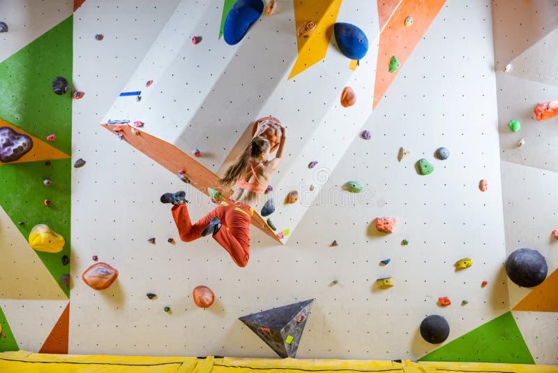 Mulher atlética nova que salta realizar de escalada no gym bouldering imagem de stock royalty free