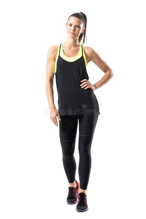 Mulher atlética nova relaxado na roupa dos esportes que anda para a câmera com mão na cintura fotos de stock