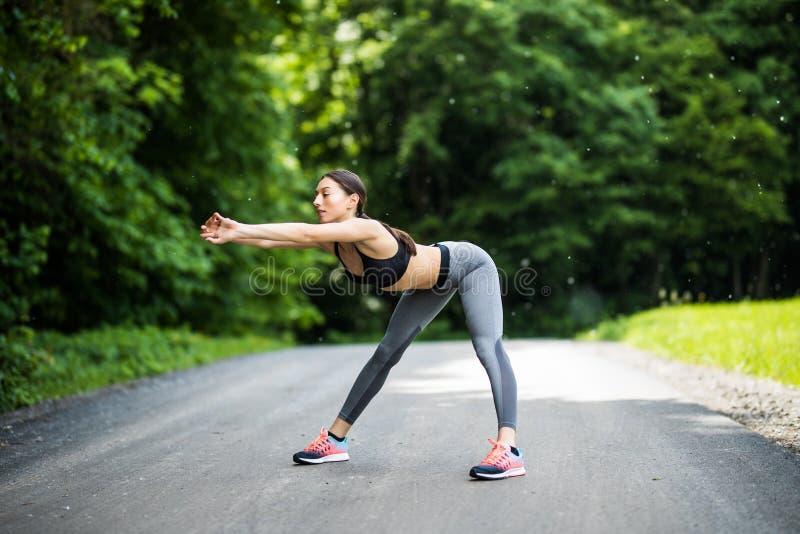 Mulher atlética que aquece-se antes de uma posição do exercício que enfrenta o e foto de stock royalty free