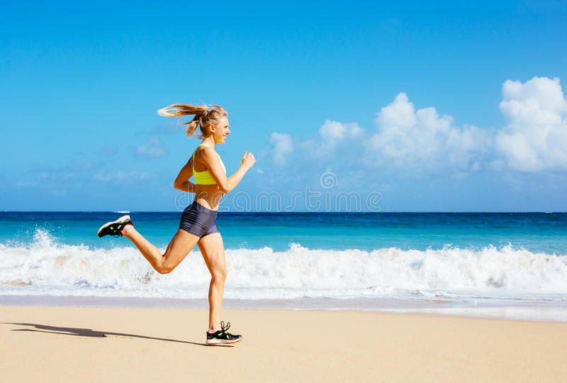 Mulher atlética que corre na praia fotografia de stock royalty free
