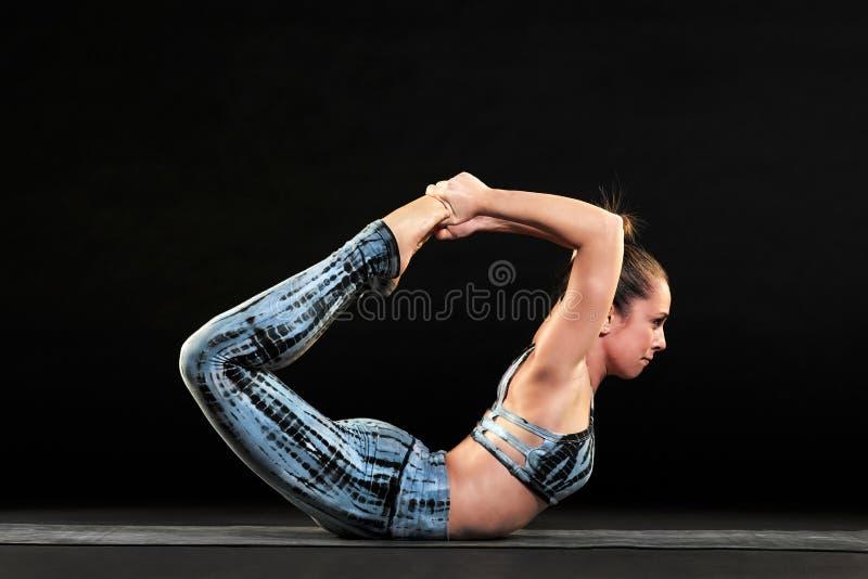 Mulher atlética que demonstra a pose da curva na ioga foto de stock