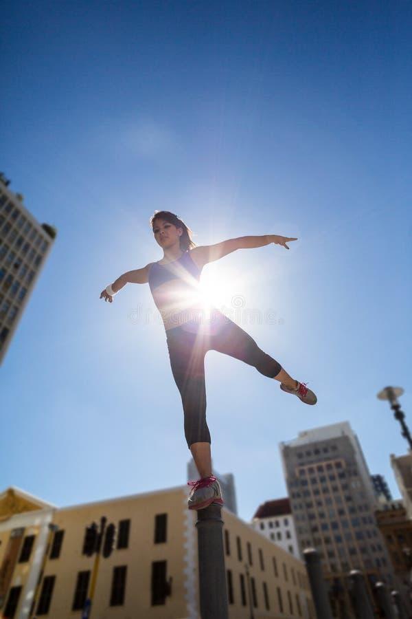 Mulher atlética que equilibra no poste de amarração e que estica para fora seu pé imagens de stock