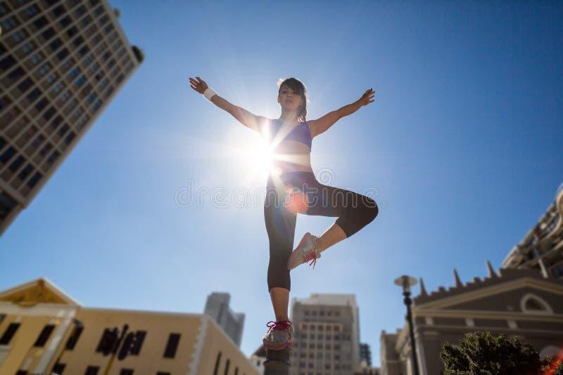 Mulher atlética que equilibra no poste de amarração e que estica para fora seus braços fotos de stock