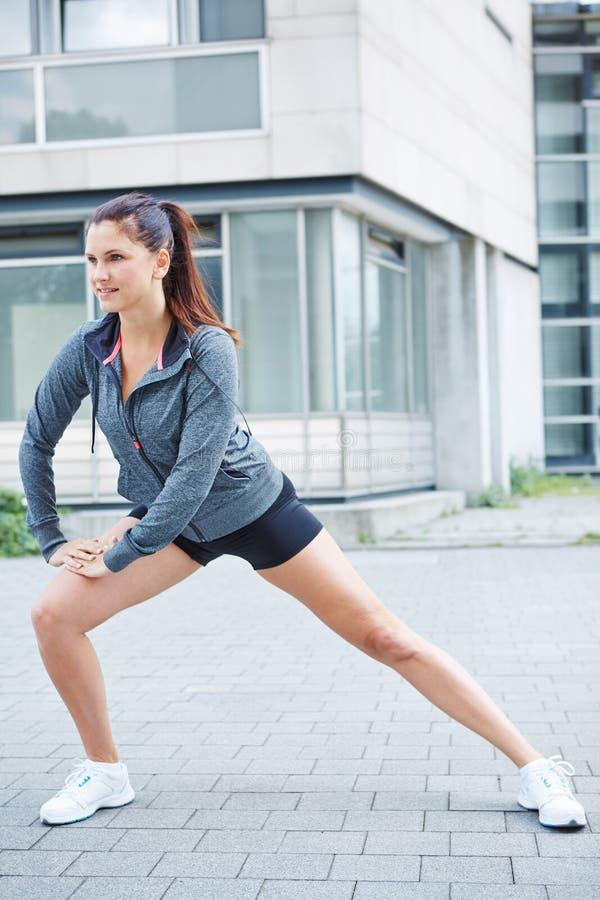 Mulher atlética que estica antes de correr imagem de stock