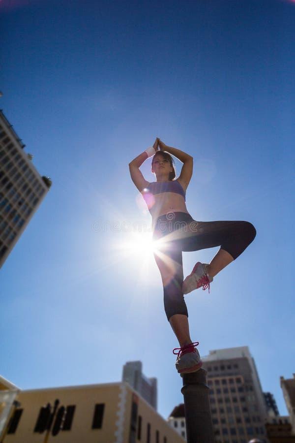 Mulher atlética que faz a ioga no poste de amarração fotografia de stock