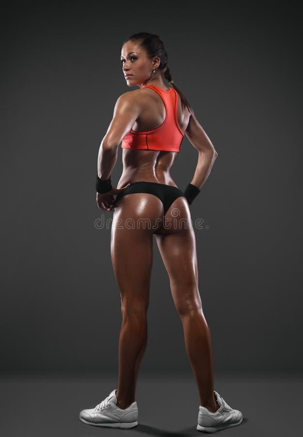 Mulher atlética que mostra os músculos da parte traseira imagens de stock