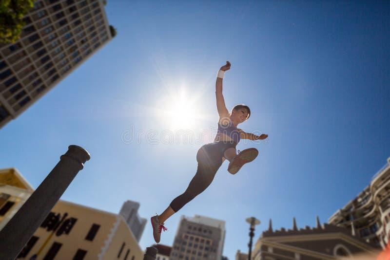 Mulher atlética que salta fora do poste de amarração imagem de stock royalty free