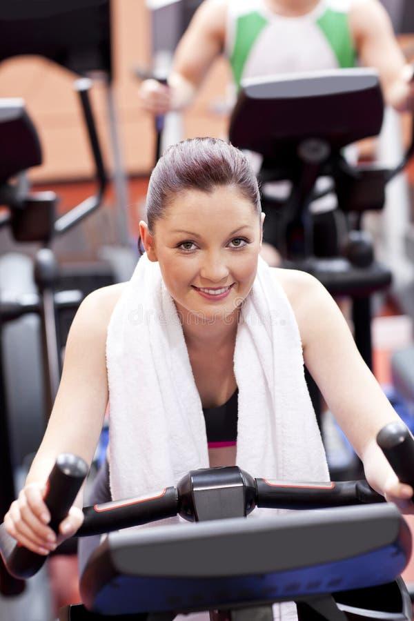 Mulher atlética que usa uma bicicleta em um centro de esporte foto de stock