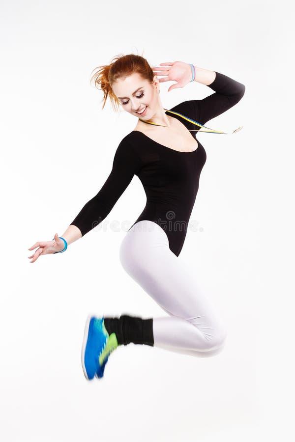 Mulher atlética ruivo nova que salta com uma medalha de ouro Felicidade, alegria, divertimento fotos de stock royalty free
