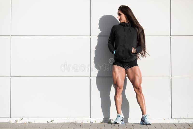 Mulher atlética 'sexy' com quadriláteros grandes Menina muscular que levanta os pés exteriores, musculares imagens de stock royalty free