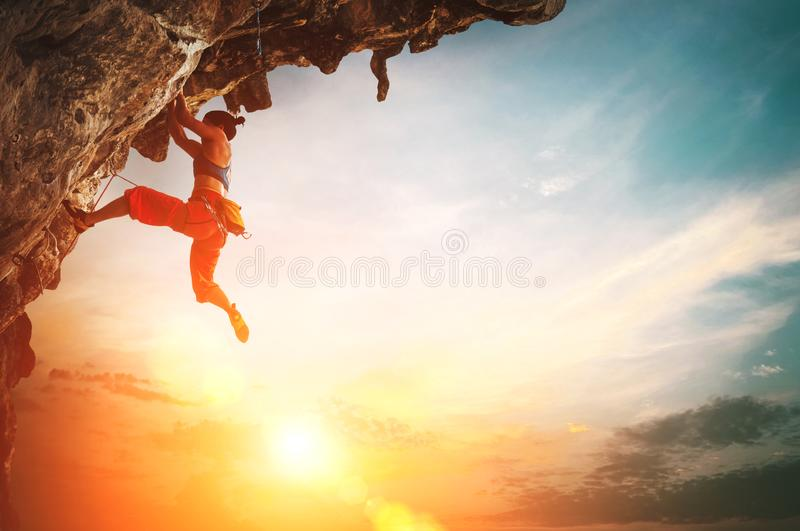 Mulher atl?tica que escala na rocha pendendo sobre do penhasco com fundo do c?u do por do sol fotografia de stock royalty free