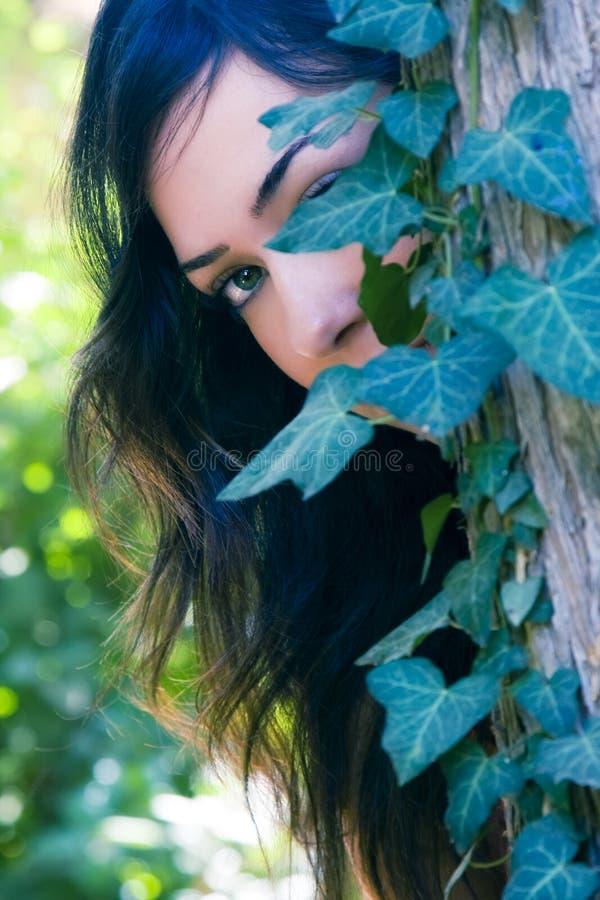 Mulher atrás das folhas imagem de stock
