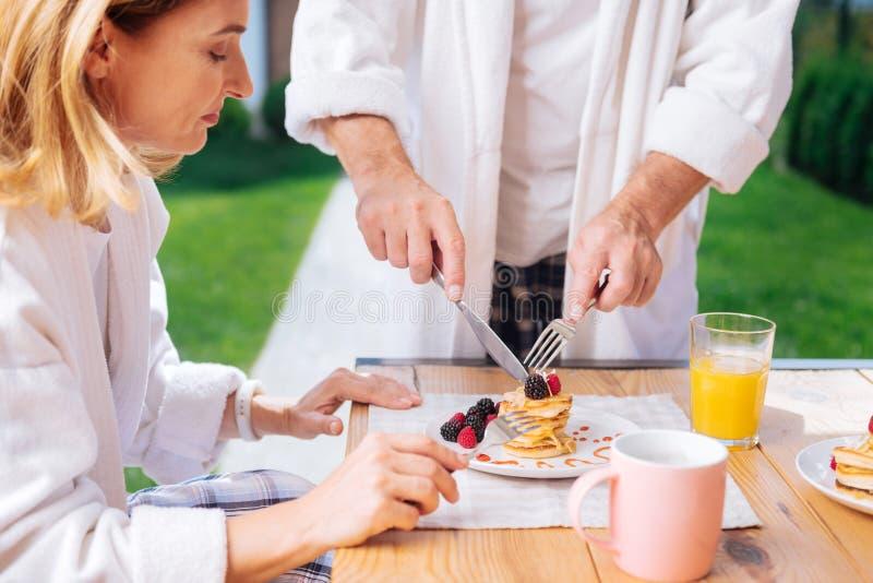 Mulher atraente madura que prova panquecas mornas com algum mel para o café da manhã fotos de stock royalty free