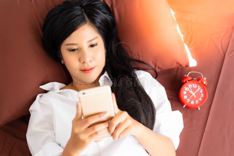A mulher atrativa acorda na manhã em uma cama A menina bonita de encantamento está jogando o Internet em linha no telefone celula foto de stock