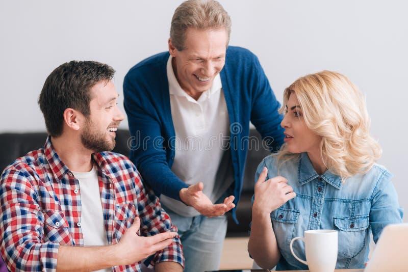 Mulher atrativa agradável que tem uma discussão com seus colegas imagens de stock