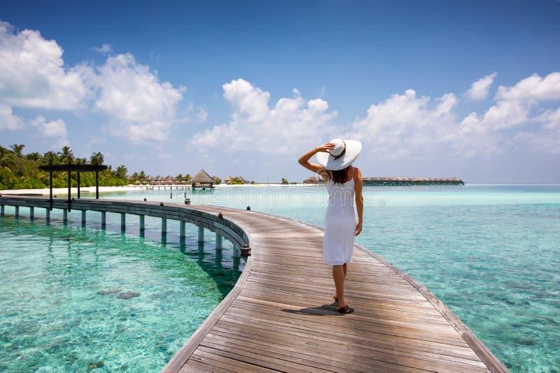 A mulher atrativa anda em um molhe de madeira em Maldivas imagens de stock royalty free