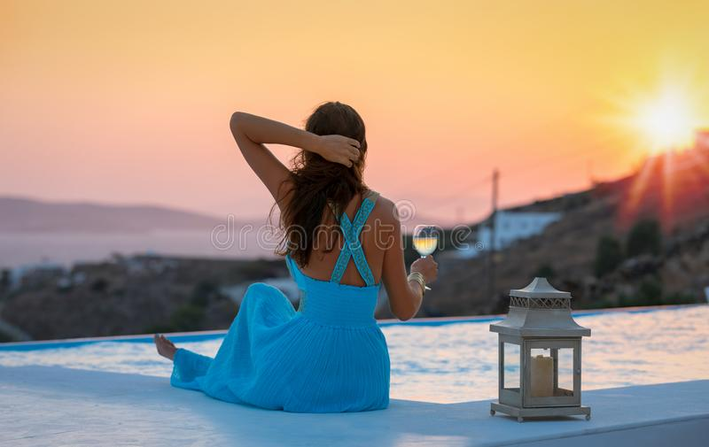 A mulher atrativa aprecia o por do sol do verão foto de stock