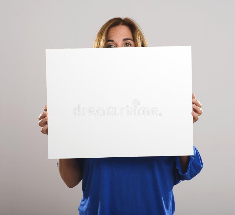A mulher atrativa com cabelo longo esconde atrás de um cartaz branco foto de stock royalty free