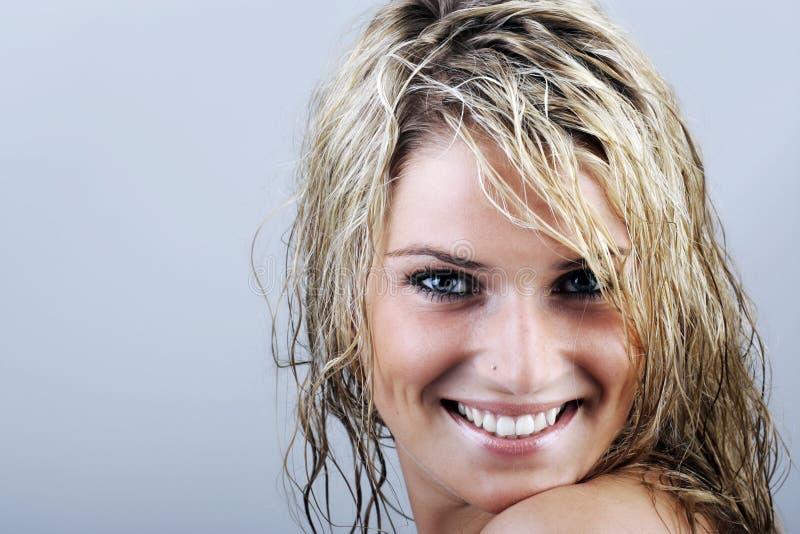 Mulher atrativa com cabelo molhado que sorri na câmera fotografia de stock royalty free