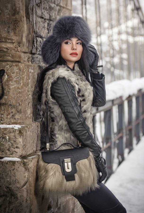 Mulher atrativa com o tampão preto da pele e o waistcoat cinzento que aprecia o inverno Ideia lateral do levantamento moreno eleg imagens de stock royalty free