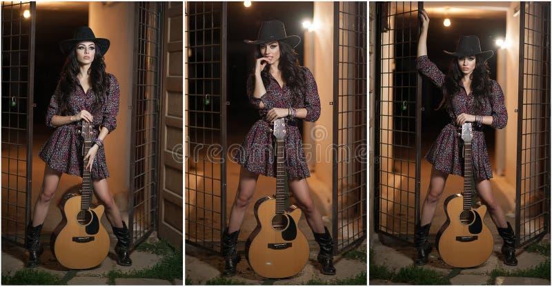 A mulher atrativa com olhar do país, disparou dentro, estilo country americano Menina com o chapéu e a guitarra pretos de vaqueir foto de stock royalty free