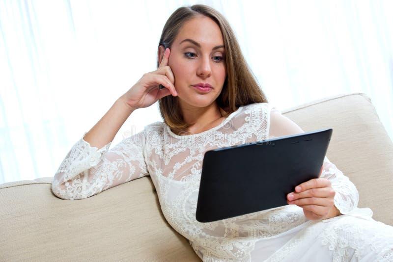 Mulher atrativa com tabuleta em casa fotografia de stock