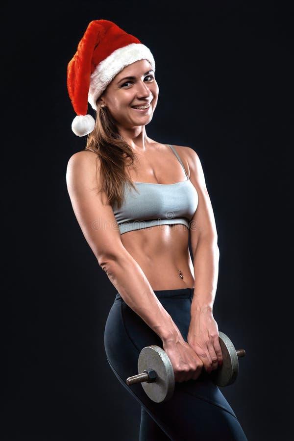 A mulher atrativa da aptidão está estando com pesos no chapéu do Natal fotografia de stock