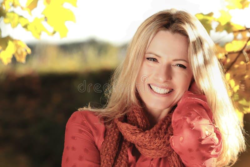 Mulher atrativa da Idade Média na frente das folhas de outono foto de stock