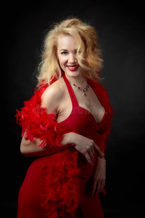 Mulher atrativa da Idade Média no vestido de nivelamento vermelho com a boa de pena macia foto de stock royalty free