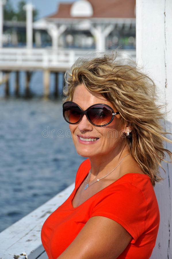 Mulher atrativa da idade nos óculos de sol que vestem a parte superior vermelha fotografia de stock royalty free