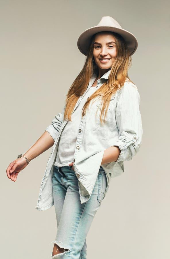 Mulher atrativa de sorriso na camisa do chapéu e da sarja de Nimes fotografia de stock