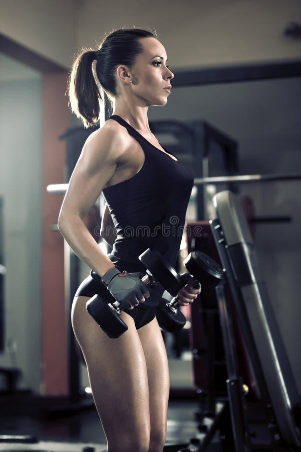 Mulher atrativa desportiva no gym com equipamento do exercício foto de stock royalty free