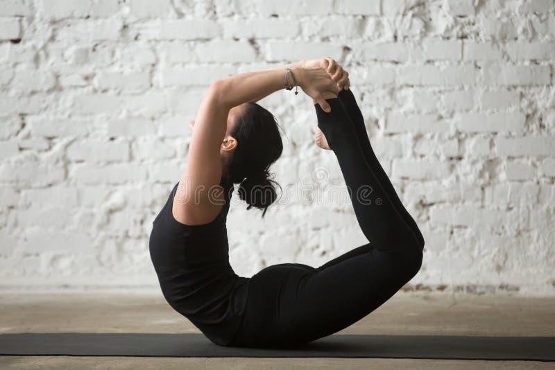 Mulher atrativa do iogue novo na pose da curva, fundo branco do sótão foto de stock