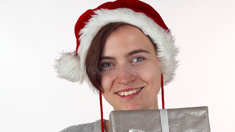 Mulher atrativa do Natal que esconde sua cara atrás de uma caixa atual fotografia de stock royalty free