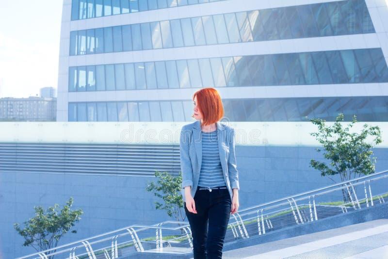 Mulher atrativa do negócio que anda abaixo da rua em um fundo de um arranha-céus fotografia de stock royalty free
