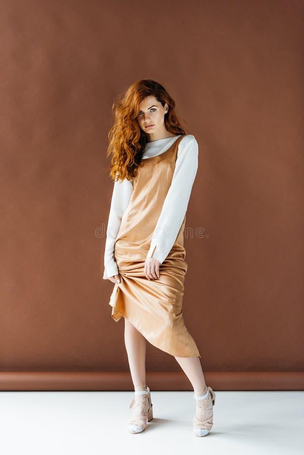 Mulher atrativa do ruivo no levantamento bege do vestido imagem de stock