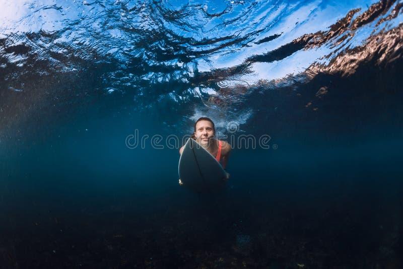 Mulher atrativa do surfista com o mergulho da prancha subaquático com abaixo a onda Mergulho do pato no oceano fotografia de stock