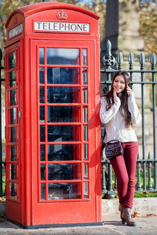A mulher atrativa do viajante de Lonodn está ao lado de uma cabine de telefone clássica, vermelha fotos de stock royalty free