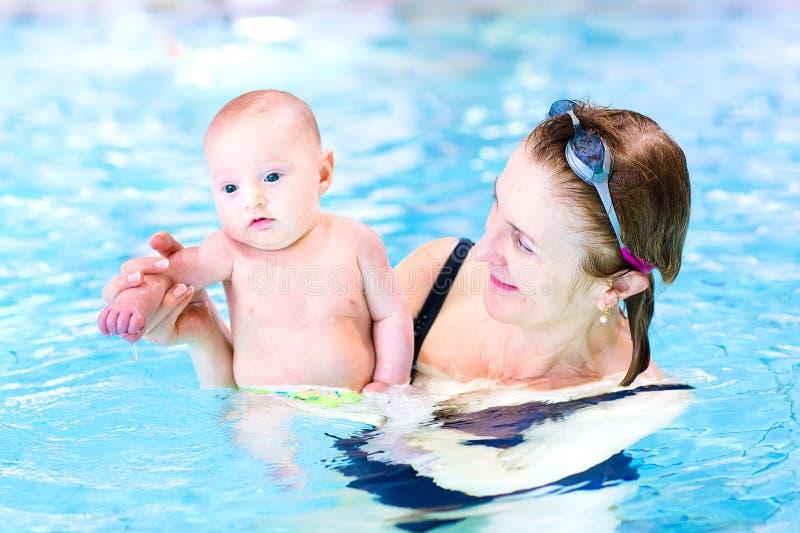 Mulher atrativa e bebê bonito na piscina fotografia de stock