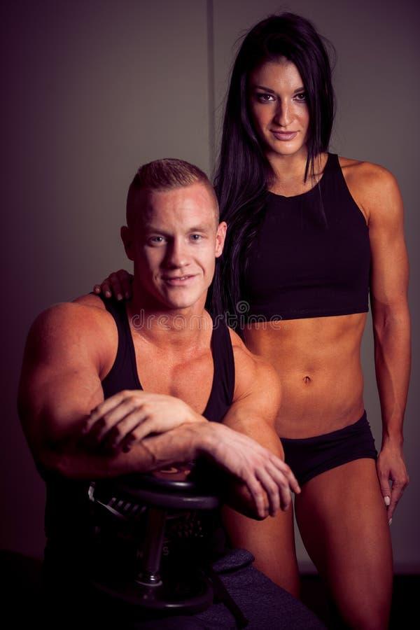 Mulher atrativa e um instrutor pessoal com treinamento do peso fotos de stock royalty free