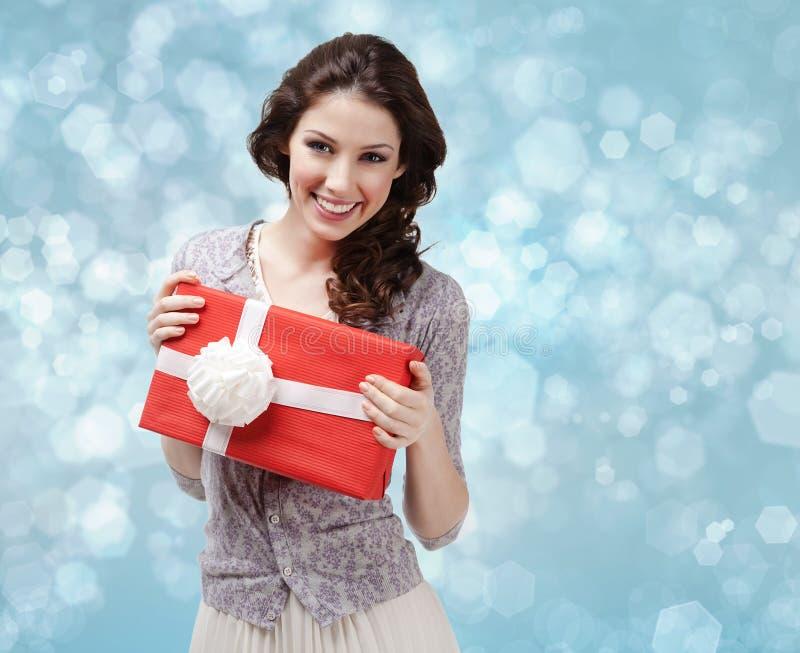 A mulher atrativa entrega um presente com curva branca fotografia de stock