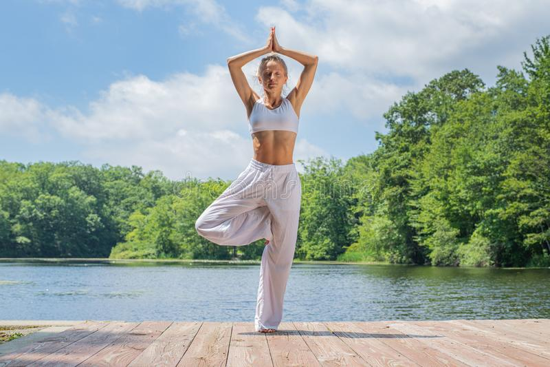 A mulher atrativa está praticando a ioga, fazendo o exercício de Vrksasana, estando na pose da árvore perto do lago foto de stock royalty free