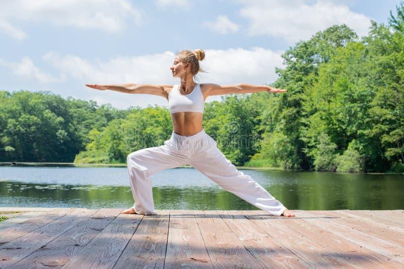 A mulher atrativa está praticando a ioga, fazendo a pose de Virabhadrasana II, estando na pose do guerreiro perto do lago fotografia de stock royalty free