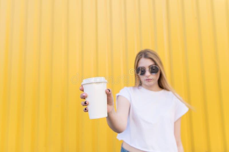 A mulher atrativa guarda uma xícara de café branca em suas mãos em um fundo amarelo Foco no copo foto de stock