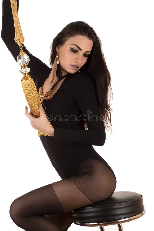 Mulher atrativa nas meias que sentam-se em uma cadeira com escova imagens de stock royalty free