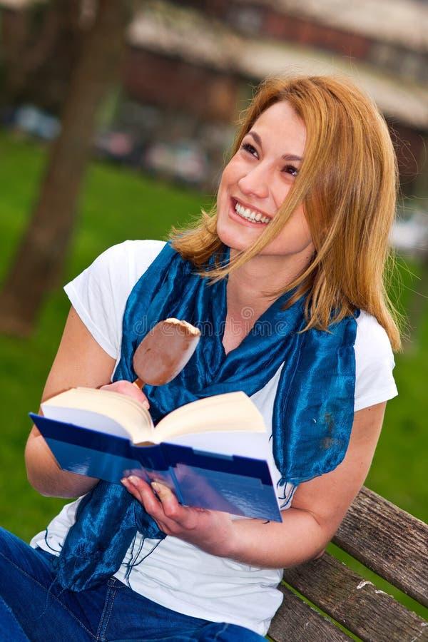 Mulher atrativa no banco com livro imagens de stock royalty free