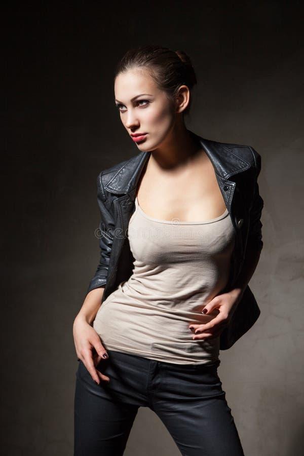 Mulher atrativa no casaco de cabedal e em calças pretos imagem de stock