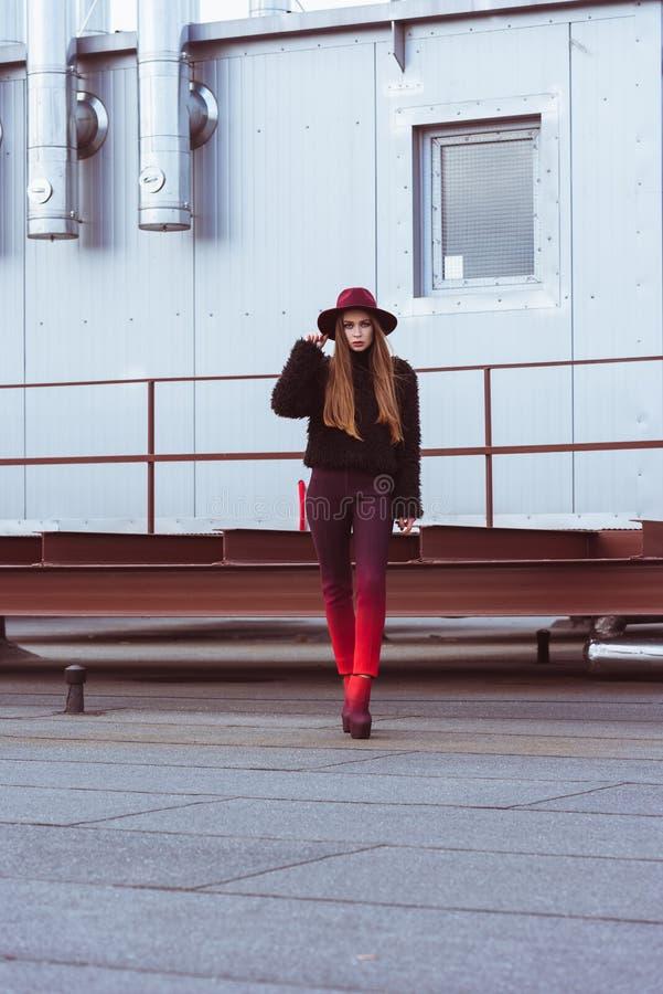 Mulher atrativa no chapéu e no vermelho de Borgonha e calças de Borgonha que está na foto de stock royalty free